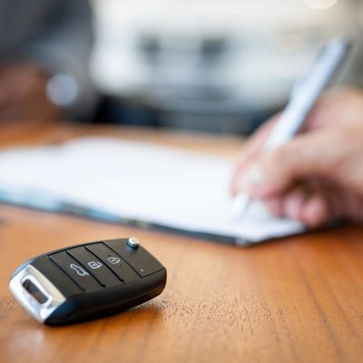 Car keys on desk with man signing purchase documents in background. Closeup of black modern car keys while hand complete the insurance policy or rental documents. Guy buying new car at dealership.